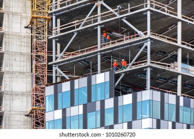 New residential and office block buildings being constructed. Industrial building site. Workers putting windows in under construction skyscraper