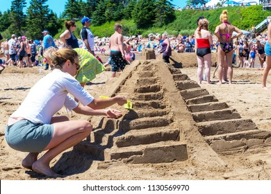 New River Beach, New Brunswick, Canada - July 7, 2018: The annual sand sculpture contest. A woman works on a sculpture of an Aztec pyramid.