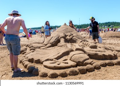 New River Beach, New Brunswick, Canada - July 7, 2018: The annual sand sculpture contest. People put the finishing touches on a sand sculpture.