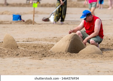 New River Beach, NB, Canada - July 27, 2019: A man uses a stick to shape his sculpture as part of the annual sand sculpture contest. The contest draws hundreds of spectators every year.