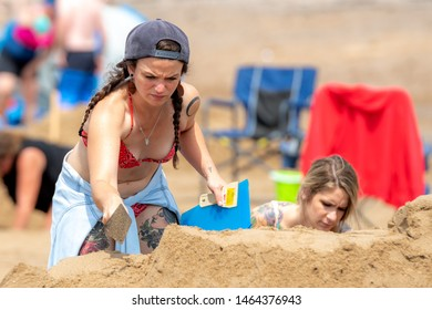 New River Beach, NB, Canada - July 27, 2019: A woman uses a trowel to shape a sand sculpture as part of the annual sand sculpture contest. The contest draws hundreds of spectators every year.