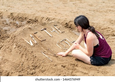 "New River Beach, NB, Canada - July 27, 2019: A woman works on a sand sculpture titled ""WE THE NORTH"" as part of sand sculpture contest. The contest draws hundreds of spectators every year."