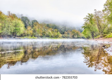 New River Gorge water river lake during autumn golden orange foliage in fall by Grandview with peaceful calm tranquil morning bright mist fog