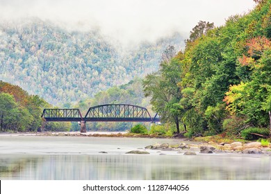 New River Gorge wide canyon, water, bridge during autumn golden orange foliage in fall by Grandview in morning fog, hills