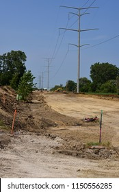 New road under construction with grading and leveling underway.