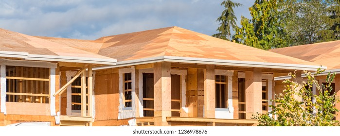 New roof of apartment building under construction on blue sky background