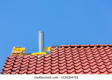 New roof with roof tiles and chimney pipe against blue sky