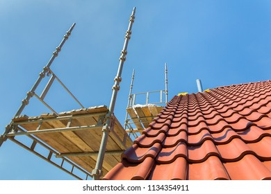 New roof tiles with scaffolding and blue sky