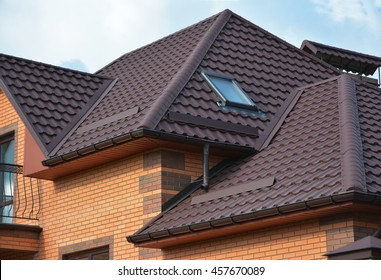 New roofing construction with attic skylights, rain gutter system, roof windows and roof protection from snow board, snow guard exterior. Modern House Construction. Hip and Valley roofing types.