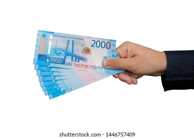 New russian bank notes with Vladivostok images on it. 2000 rubles denomination in man's hand isolated on white background. Hand giving banknotes in financial, money exchange and donation concepts.