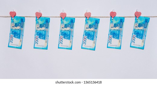 New russian money banknotes of two thousand roubles hanging on clothesline by clothespins on white background. Success in business, finance, wealth concept