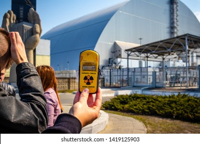 The New Safe Confinement arch over desaster reactor nr 4 in Chernobyl, Ukraine with a Geiger Counter and tourists in front