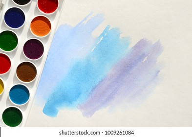 A new set of watercolors lies on a sheet of paper, which shows an abstract watercolor drawing in the form of blue strokes. The concept of amateur painting among teenagers