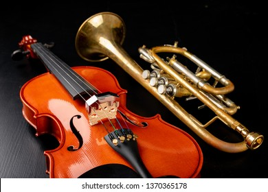 A new shining violin and an old trumpet on a dark table. Musical instruments, stringed and wind. Black background.