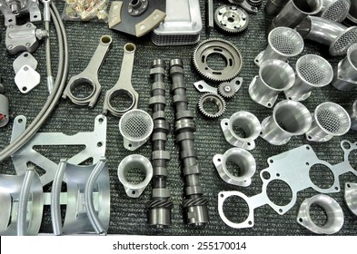 New and shiny part of rally car engine on a table in workshop:  clutch, connecting rod from a car engine, piston, camshaft and more.