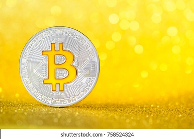 New shiny silver bitcoin coin with golder bitcoin B symbol on golden glitter background with copy space