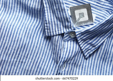 New shirt and rfid sticker tag represent fashion retail shoplifting protection technology concept.