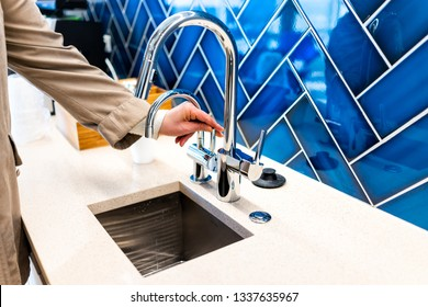 New small modern faucet and kitchen sink closeup with woman turning on handle and blue vibrant backsplash and shiny clean stainless steel handle