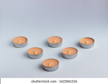 New small round wax candles on a white and gray background. Colored scented Spa candles. Minimal design.