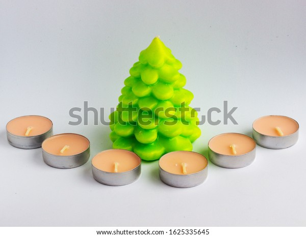 New small round wax candles and candle in the form of a fir tree on a white and gray background.  Minimal design.