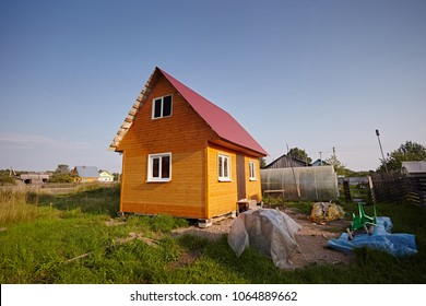 New small wooden house with sundeck, the walls of the yellow blockhouse, the roof covered with red metal tile