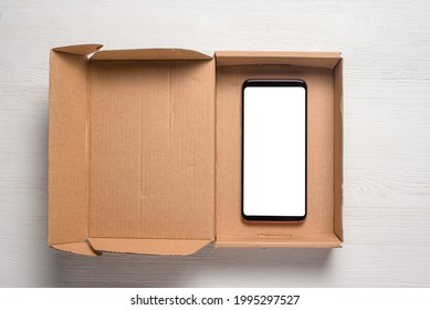 New smartphone with blank screen with a copy space in the brown cardboard box flat lay background. Free shipping.
