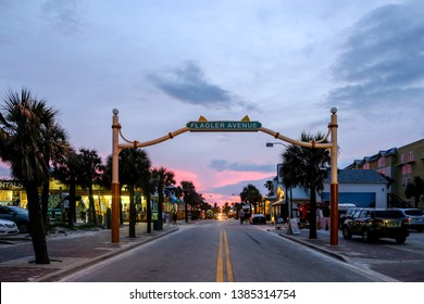 New Smyrna Beach, FL / USA - June 10th, 2017: Flagler Avenue sign at the beach entrance in New Smyrna Beach on a summer evening.