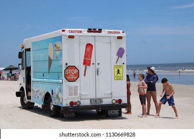 New Smyrna Beach, Florida / USA - 06/25/2018: Ice cream truck stopped for customers on beach.