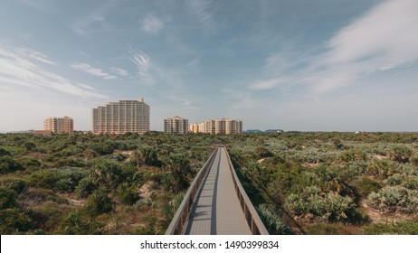 New Smyrna Dunes Park in New Smyrna Beach, Florida. Boardwalk to the beach through dunes and scrub.  Condos in tha background.