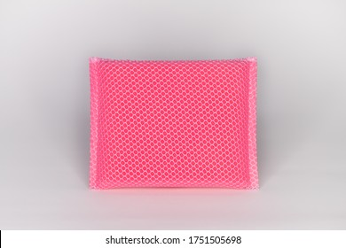 New sponge for washing dishes. Pink sponge with mesh covering the sponge and white background.