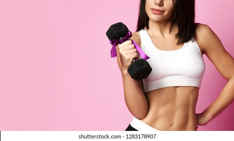 New spring sport workout concept for woman day 8 march. Girl working out with big weight dumbbell smiling on pink background