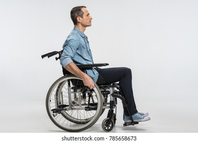 New start. Thoughtful concentrated handicapped man touching wheels and sitting in profile while moving ahead