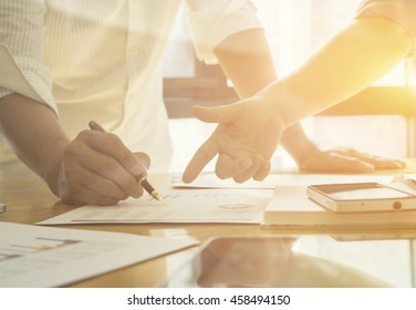 New startup business project,Business meeting time,account managers crew working with new startup project,pointing hands,Laptop Notebook on wood table.analyze plans,vintage tone,morning light flare