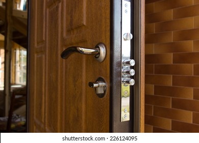 New steel three bolt door lock installed on the wooden front door of a new build house showing the three individual cylinders of the lock