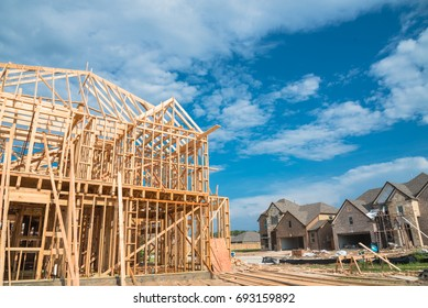 New stick built home under construction and blue sky in US. Framing structure/wood frame of wooden houses next to completed suburban home. Pile of sand, gravel, logs in front. Industrial, real estate