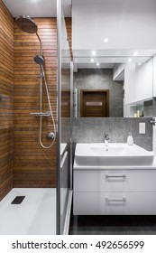 New style bathroom with wooden wall, shower, mirror and basin