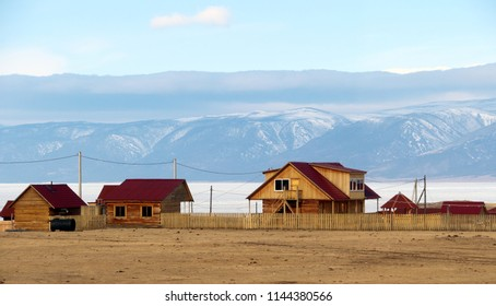 New style houses on Olkhon island. Made in wooden log style with red roof. Located nearby Baikal lake in front of mountains taken in late winter