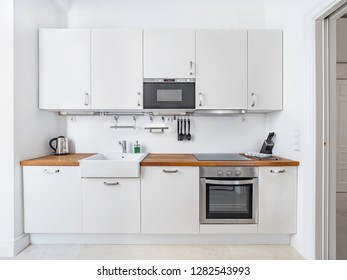 New stylish bright kitchen with white cabinets. Spacious modern interior
