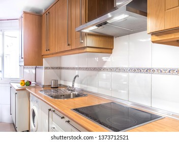 New stylish bright kitchen with wooden cabinets. Spacious modern fully equipped appliance interior with wooden desk, ceramic stove and  big windows