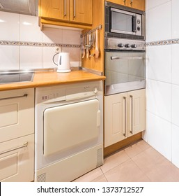 New stylish bright kitchen with wooden cabinets, microwave and oven. Spacious modern fully equipped appliance interior with wooden desk, ceramic stove and  big windows