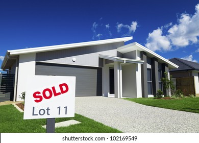 New suburban Australian house with large SOLD sign.