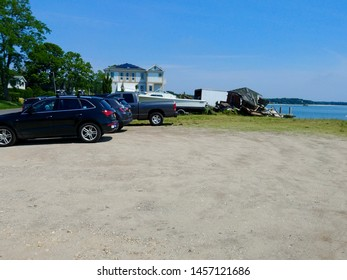 New Suffolk, NY - July 4 2019: Cars parked in a dirt lot in downtown New Suffolk