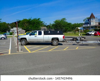 New Suffolk, NY - July 4 2019: A pickup truck with a boat trailer parked in the New Suffolk Beach parking lot