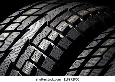 New SUV winter tyres on a black background. Shallow DOF. Studio shot.