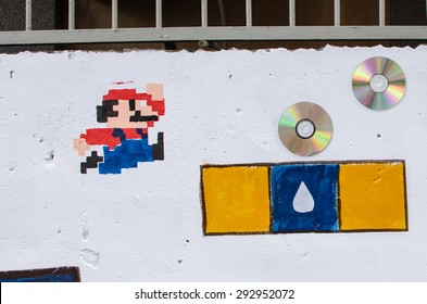 New Taipei City, Taiwan - 18 October 2014: residents of local community paint Mario jumping on white wall. The aim of the painting is to bring vitality to the community.