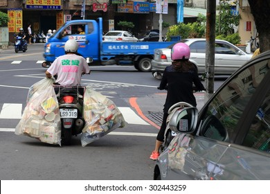 New Taipei City, Taiwan - August 1, 2015: A man riding a motorcycle carrying two big bags of recycling garbage.