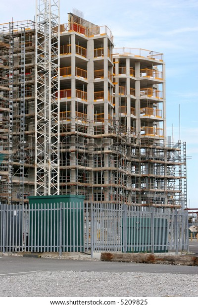 New tall building under construction with scaffolding, against a pale blue sky.