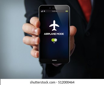 new technologies concept: businessman hand holding a 3d generated touch phone with airplane mode on the screen. Screen graphics are made up.