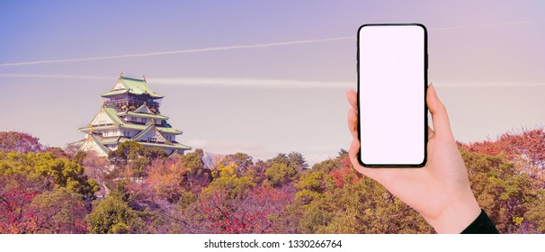 new technology and application support travel concept from beauty business woman hand show new smart phone with osaka castle and tree in osaka park at osaka japan autumn season travel