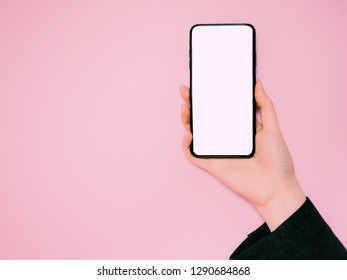 new technology and e-commerce concept from hand of business woman in suit hold and show new smart phone on isolated pink pastel background with copy space and clipping path